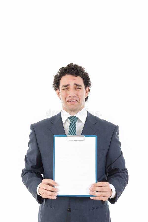 Homme d'affaires tenant la table des messages blanche vide avec l'expressio triste photos stock