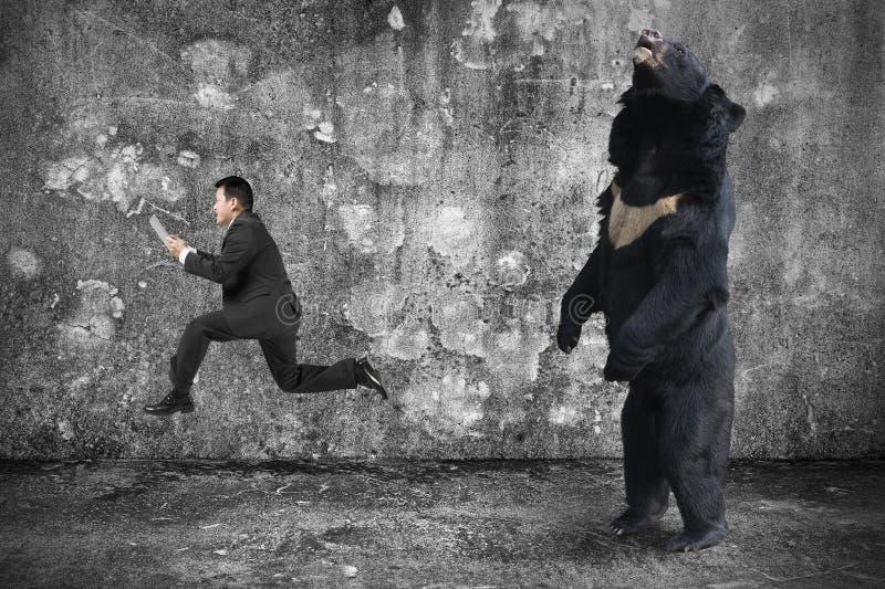 Homme d'affaires tenant le comprimé fonctionnant d'un ours fâché image stock