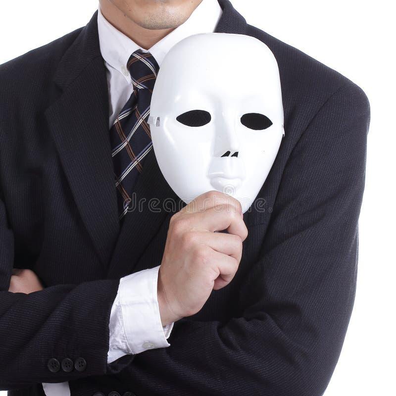 Homme d'affaires tenant le masque blanc photographie stock