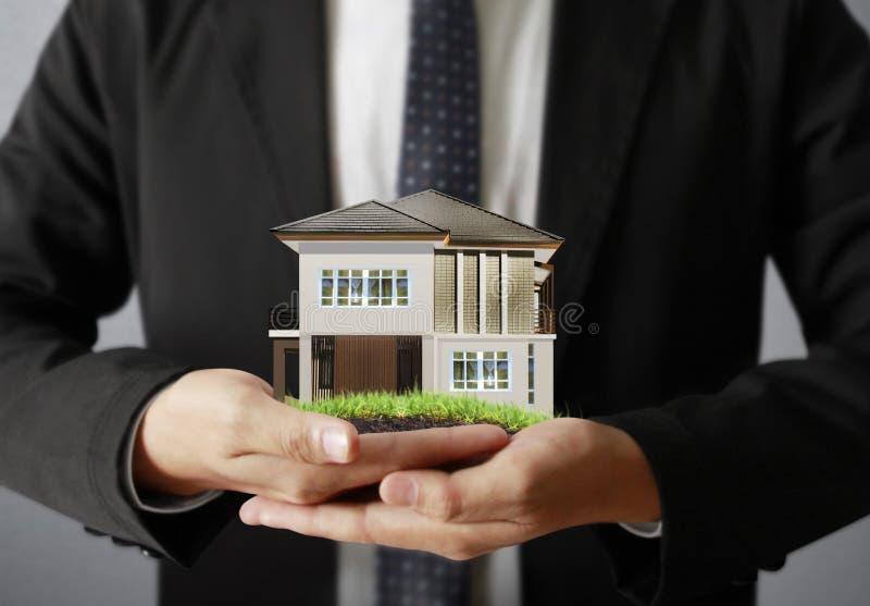Homme d'affaires tenant le modèle de maison photographie stock