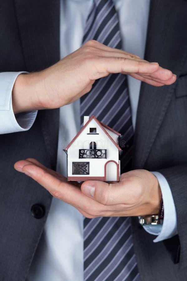 Homme d'affaires tenant le modèle de maison images libres de droits