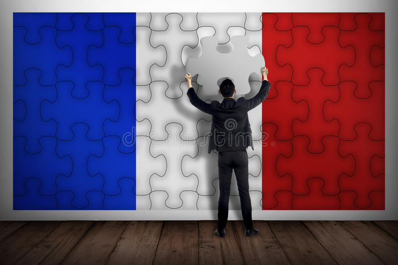 Homme d'affaires tenant le morceau de puzzle, faisant le drapeau français image stock