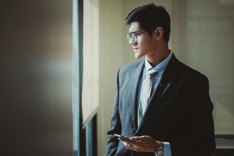 Homme d'affaires tenant le téléphone intelligent dans le bureau Concept de planification image stock