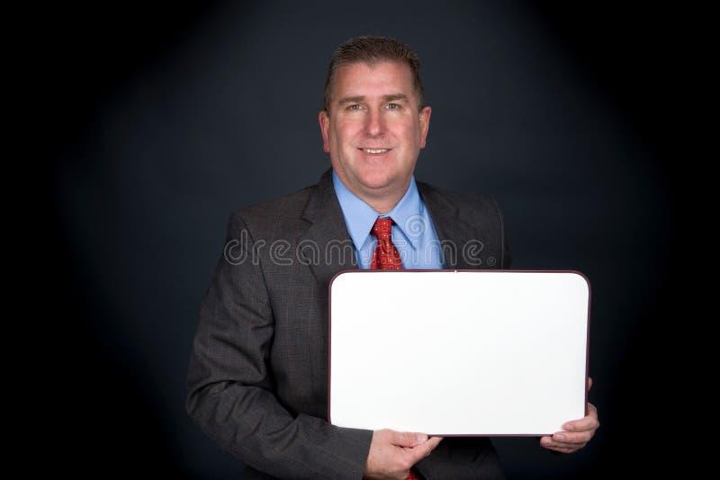 Homme d'affaires tenant le tableau blanc image stock