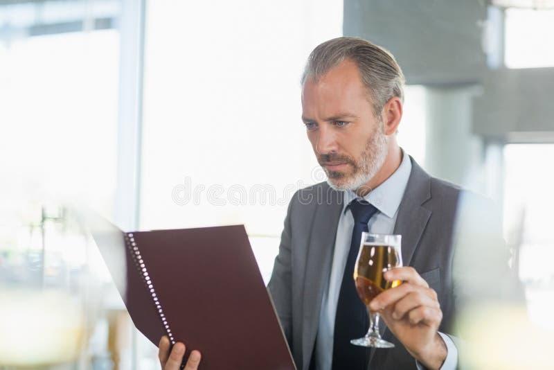 Homme d'affaires tenant le verre de bière et regardant le menu images stock
