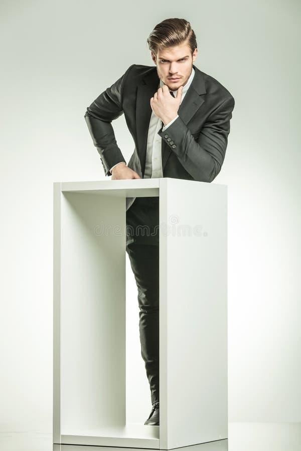 Homme d'affaires tenant sa main sur son menton, pensant image libre de droits