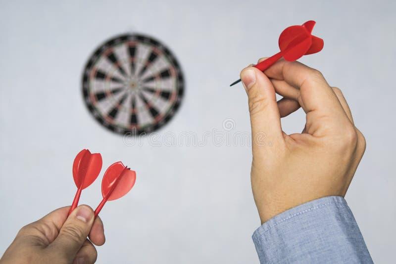 Homme d'affaires tenant un dard visant la cible - optimisation d'affaires, visant, concept de foyer Heurtez la cible Succ?s dans  image libre de droits
