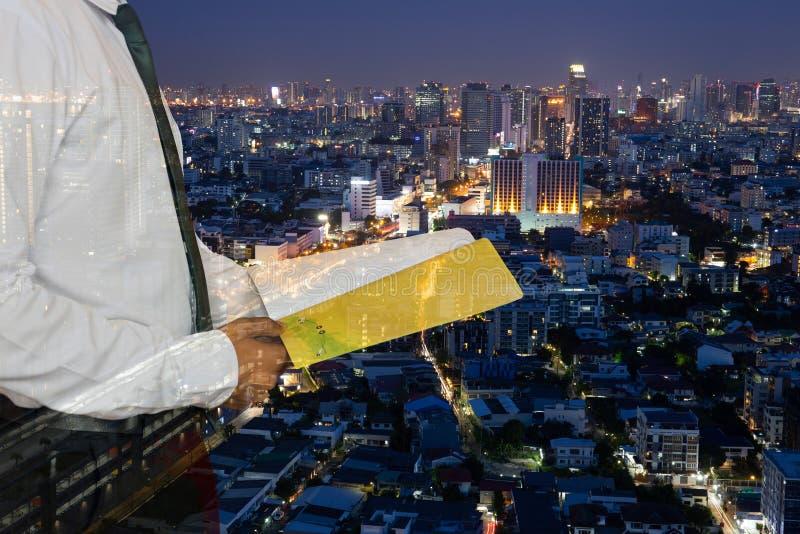 Homme d'affaires tenant un livre se tenant contre le backgroun de ville de nuit photos stock