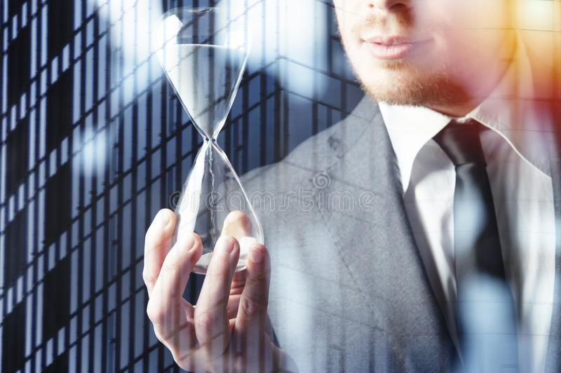 Homme d'affaires tenant un sablier Concept de date-butoir dans les affaires images stock