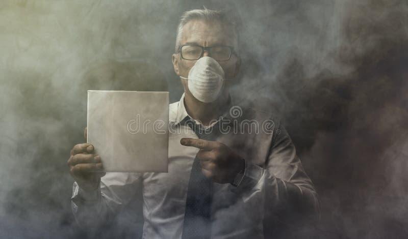 Homme d'affaires tenant un signe et une pollution atmosphérique photos stock