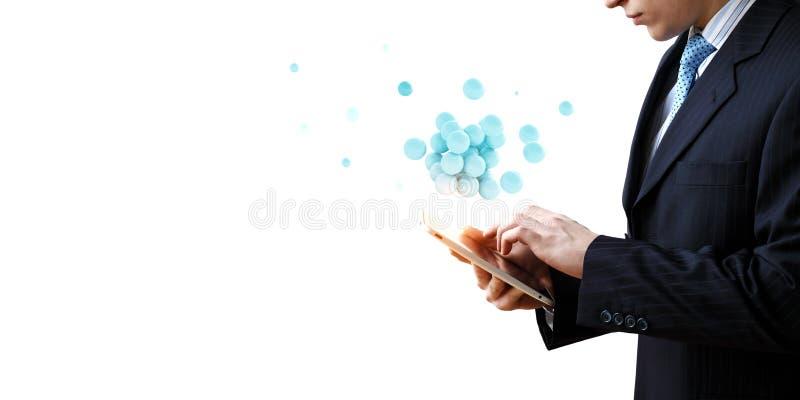 Homme d'affaires tenant un tabalet avec un groupe de sph?res faisant de la l?vitation en haut Media m?lang? photos stock