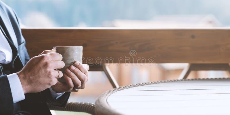 Homme d'affaires tenant une tasse de thé chaud entre les mains, sur la terrasse du café Séjour de travail, moment d'harmonie et d photographie stock libre de droits