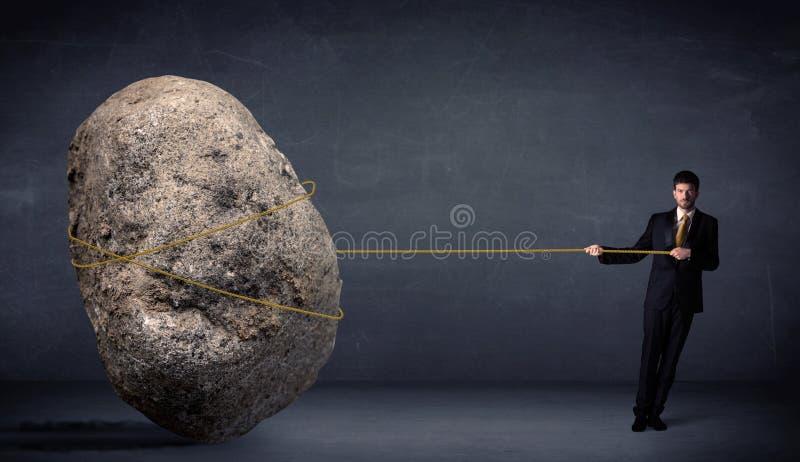 Homme d'affaires tirant la roche énorme avec une corde photographie stock libre de droits