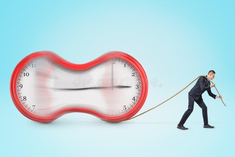 Homme d'affaires tirant une horloge étirée avec une corde sur le fond bleu photo stock