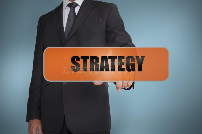 Homme d'affaires touchant la stratégie de mot photos stock