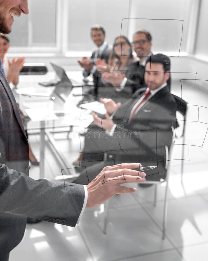 Homme d'affaires traçant un diagramme de commercialisation sur un conseil de verre photos libres de droits