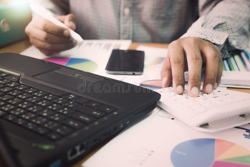 Homme d'affaires travaillant à la calculatrice dans le bureau photographie stock libre de droits