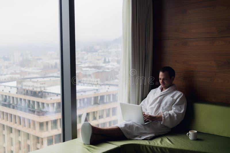 Homme d'affaires travaillant à la maison ou dans le voyage Portrait de vue de côté du jeune homme d'affaires beau s'asseyant sur  photo libre de droits
