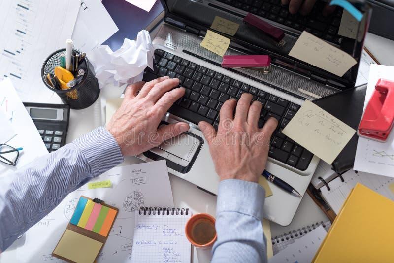 Homme d'affaires travaillant à un bureau encombré et malpropre photos libres de droits