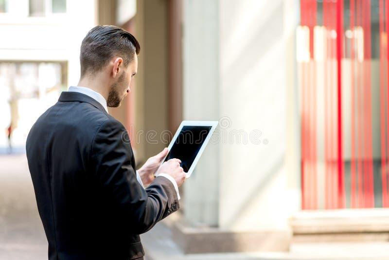 Homme d'affaires travaillant au comprimé Jeune homme à l'arrière de tenue de soirée image stock