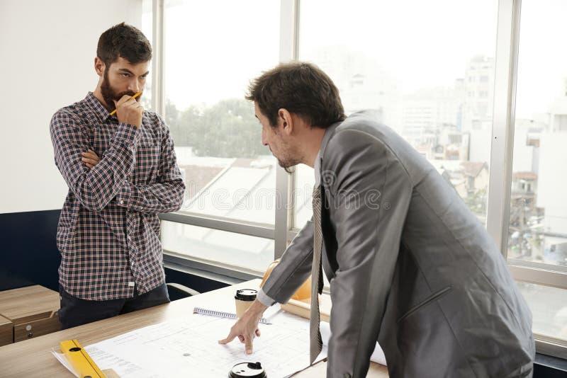 Homme d'affaires travaillant avec l'ingénieur au bureau photos stock