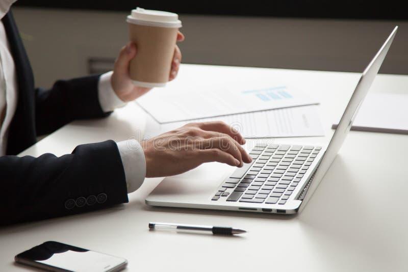 Homme d'affaires travaillant avec l'ordinateur portable et les documents sur le lieu de travail, clos photographie stock