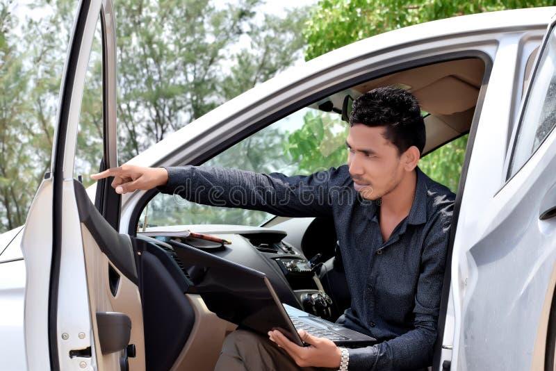 Homme d'affaires travaillant avec l'ordinateur portable et s'asseyant dans la voiture photos libres de droits