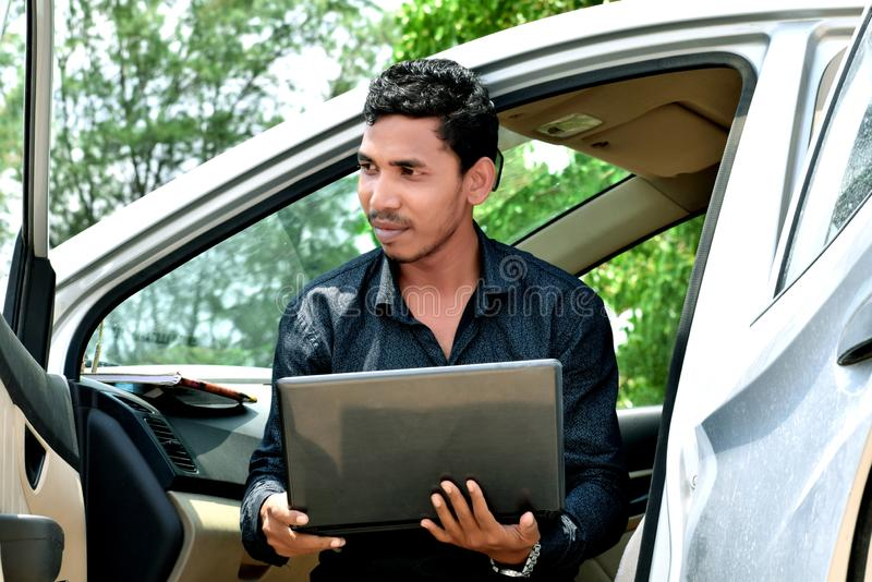 Homme d'affaires travaillant avec l'ordinateur portable et s'asseyant dans la voiture photos stock