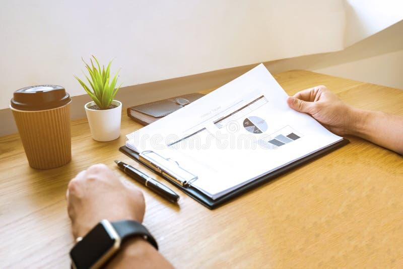 Homme d'affaires travaillant avec le document de rapport des revenus de résultats sur le bois t photographie stock
