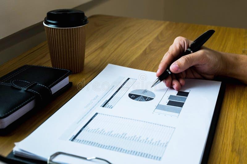 Homme d'affaires travaillant avec le document de rapport des revenus de résultats sur le bois t photo libre de droits