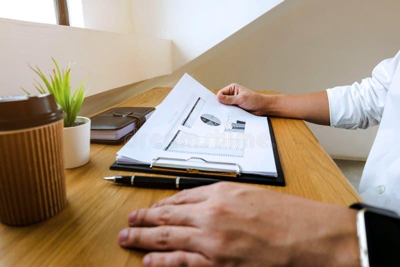 Homme d'affaires travaillant avec le document de rapport des revenus de résultats sur le bois t photos stock