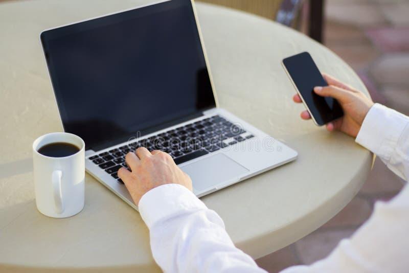Homme d'affaires travaillant avec le téléphone portable et l'ordinateur portable et la tasse de café photographie stock libre de droits