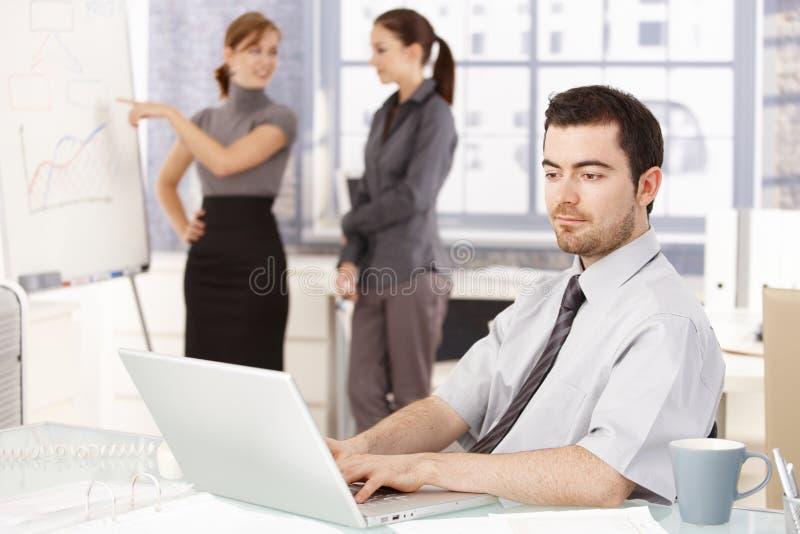 Homme d'affaires travaillant dans des femmes de bureau à l'arrière-plan image stock