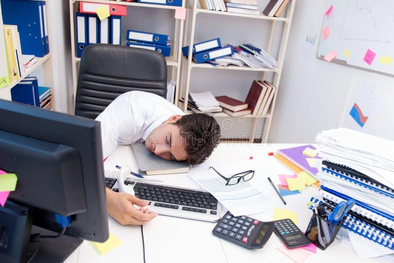 Homme d'affaires travaillant dans le bureau avec des piles des livres et des papiers image libre de droits