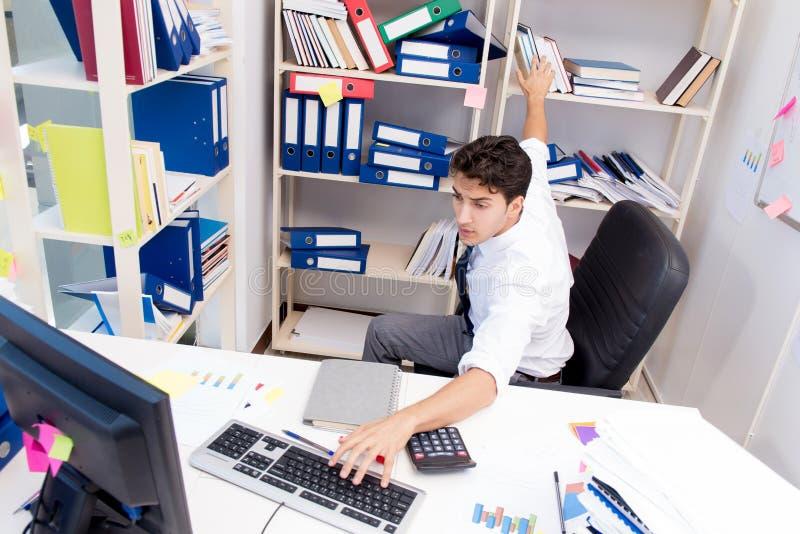 Homme d'affaires travaillant dans le bureau avec des piles des livres et des papiers photo libre de droits
