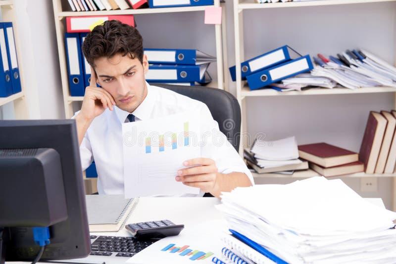 Homme d'affaires travaillant dans le bureau avec des piles des livres et des papiers photographie stock libre de droits