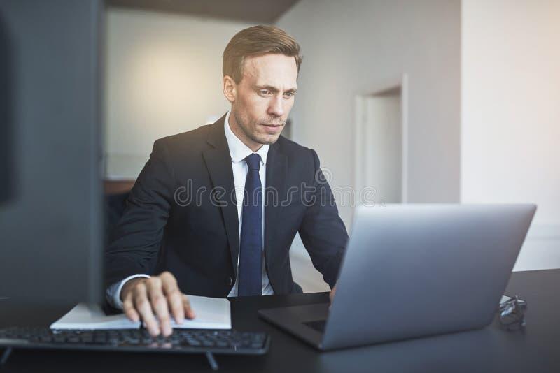 Homme d'affaires travaillant en ligne avec un ordinateur portable à son bureau photo stock