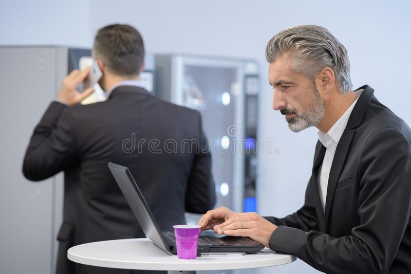 Homme d'affaires travaillant pendant les pauses café photographie stock libre de droits