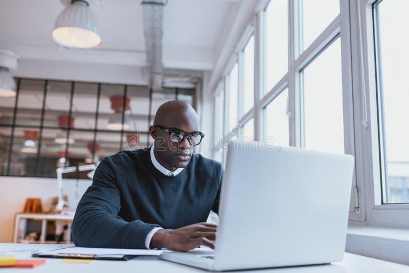 Homme d'affaires travaillant sur l'ordinateur portable dans le bureau image stock