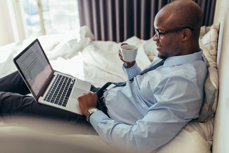 Homme d'affaires travaillant sur l'ordinateur portable se trouvant sur le lit photographie stock libre de droits