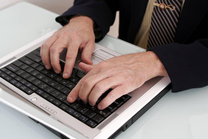 Homme d'affaires travaillant sur un ordinateur portable photos stock