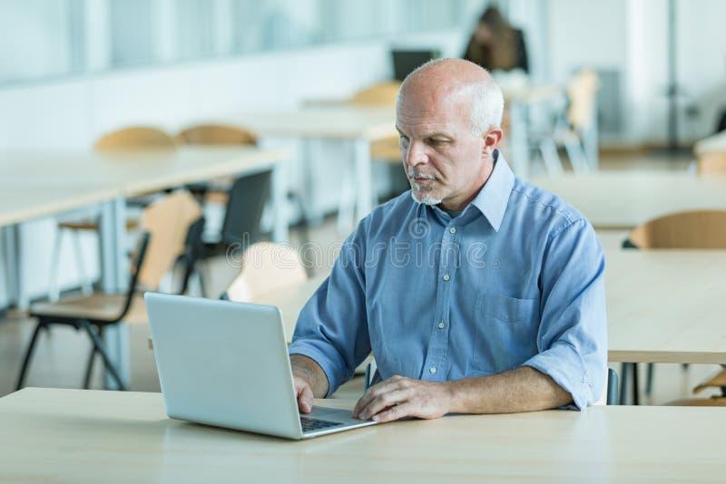 Homme d'affaires travaillant sur un ordinateur portable dans une cantine photos libres de droits