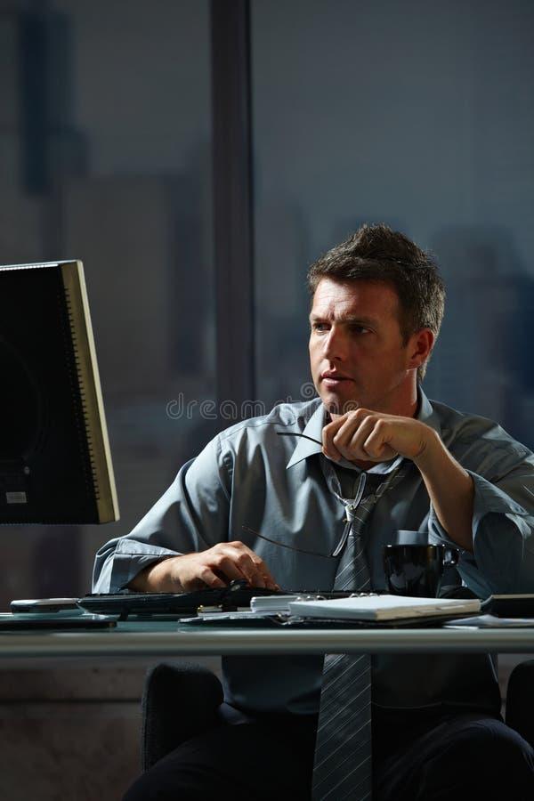 Homme d'affaires travaillant tard dans le bureau photographie stock