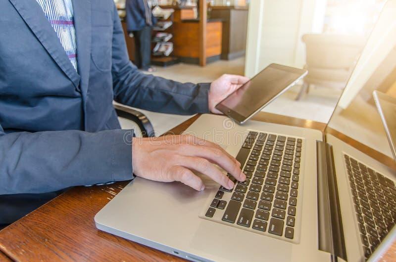 Homme d'affaires travaillant utilisant Ipad tout en travaillant avec l'ordinateur portable photos stock