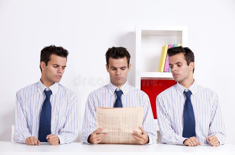 Homme d'affaires trois affichant un journal photographie stock