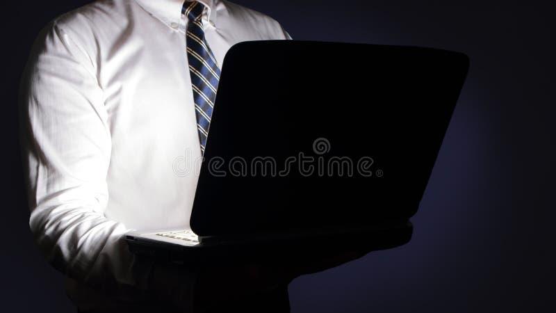 Homme d'affaires Typing sur l'ordinateur portable dans l'obscurité images stock