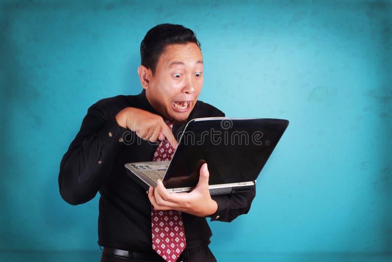 Homme d'affaires Typing sur l'ordinateur portable, expression enthousiaste drôle photo libre de droits