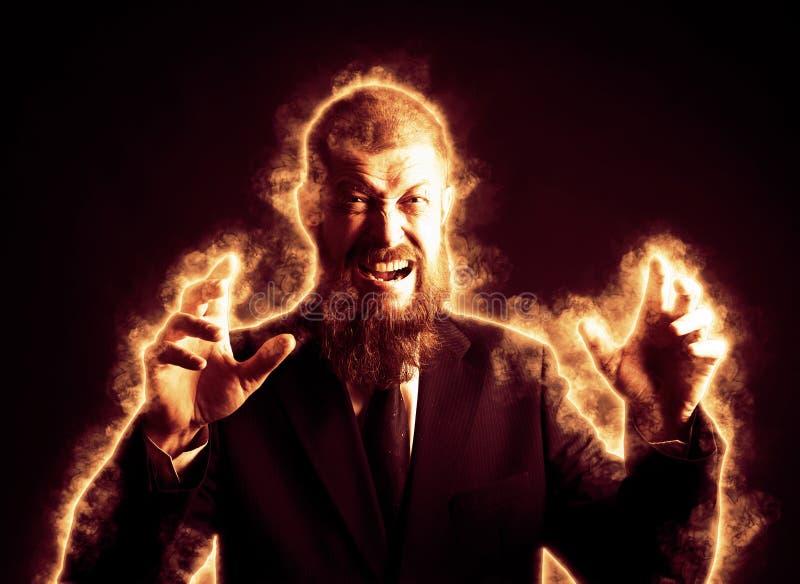 Homme d'affaires d'une cinquantaine d'années et barbu dans une rage, fâché, brûlant en feu, patron dans une flamme photographie stock libre de droits