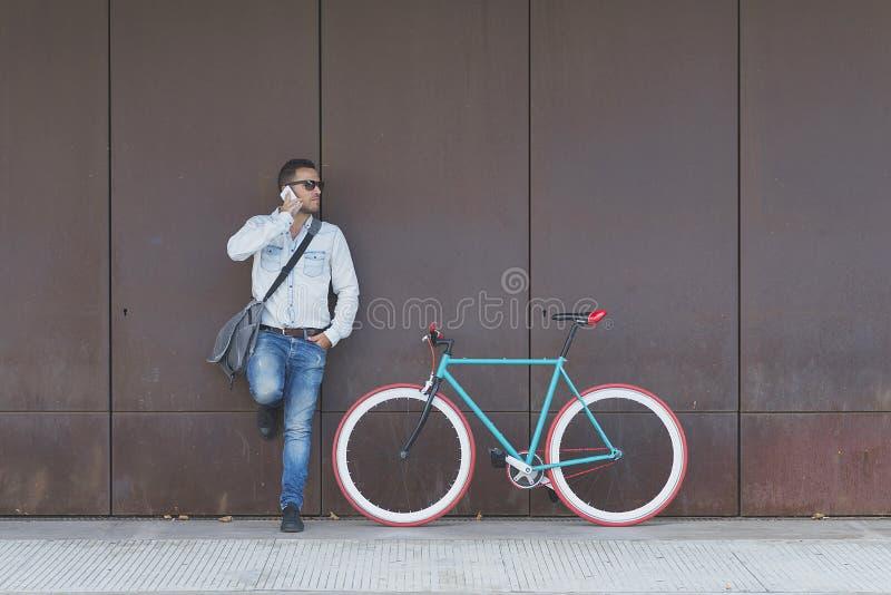Homme d'affaires urbain élégant se tenant sur rue appelle image stock
