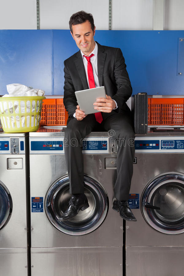 Homme d'affaires Using Digital Tablet dans la blanchisserie photos stock